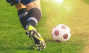 Closeup of soccer ball and player wearing cleats